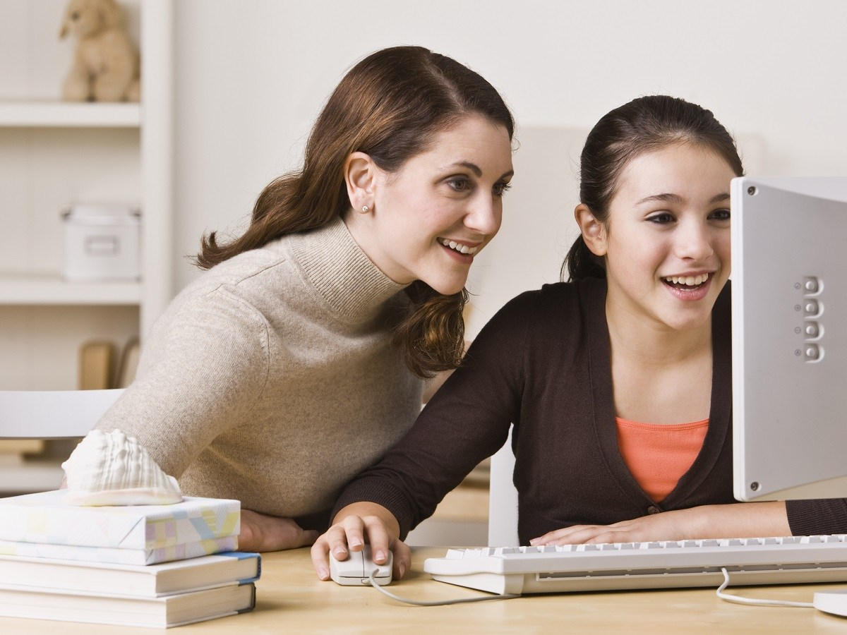 A mother and daughter using a computer together